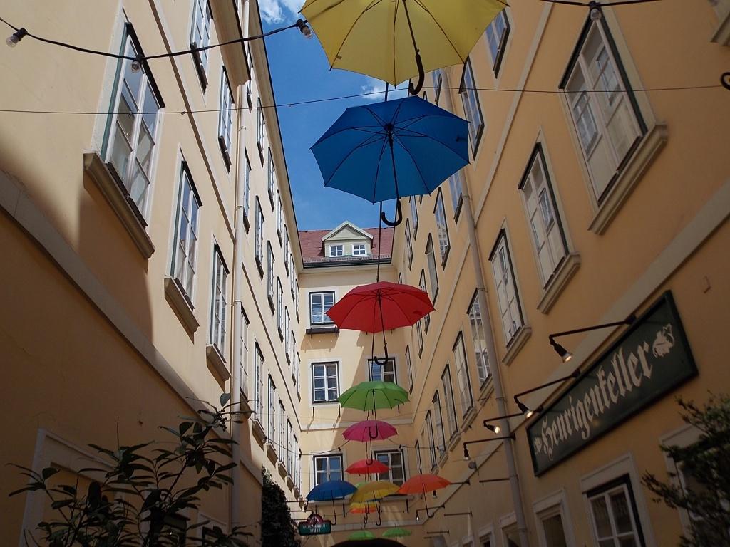 Wien Sünnhof eine alte Passage und in der Luft hängen uni farbene Regenschirme.
