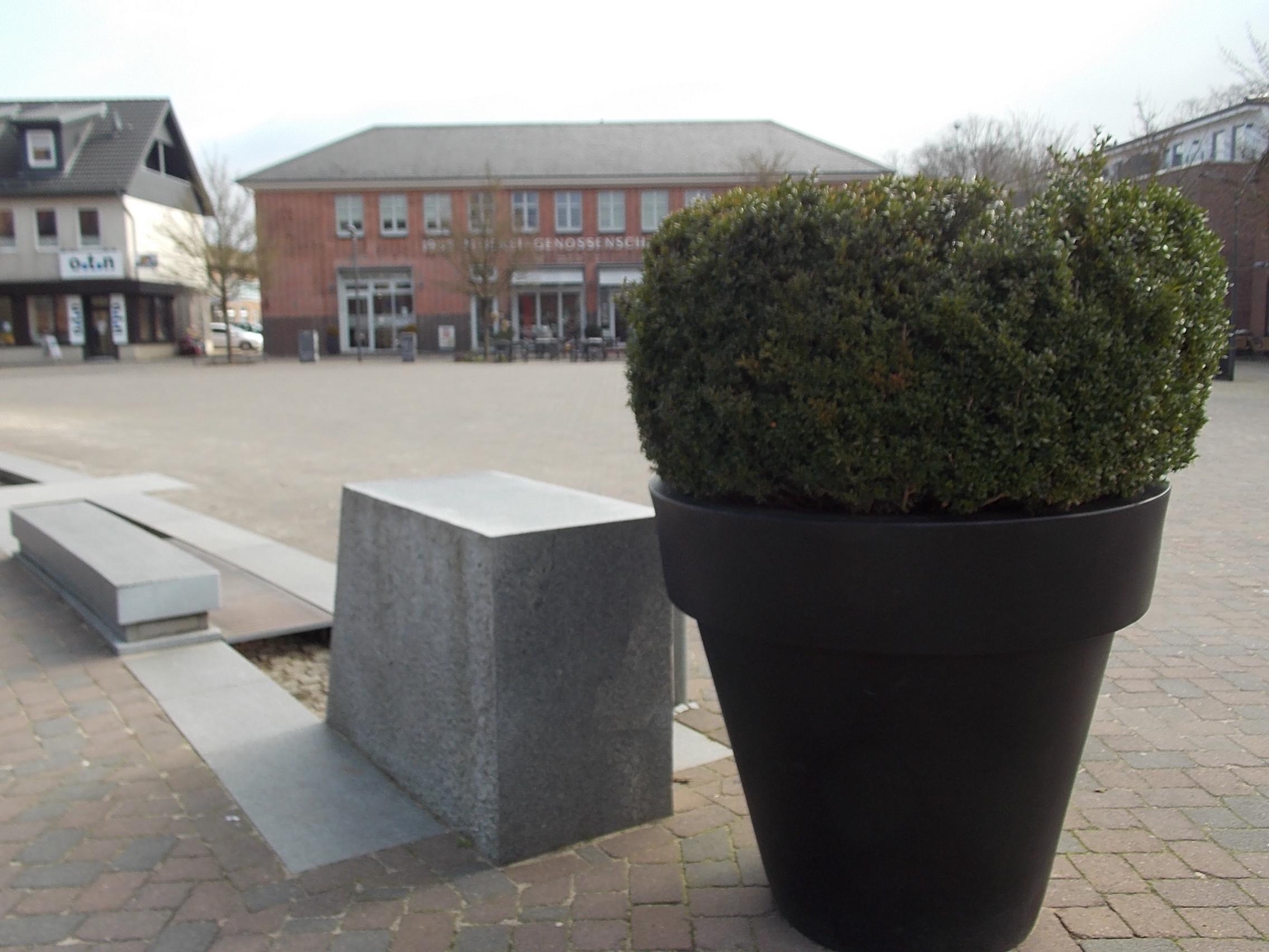 Nortorf Marktplatz, vorne steht ein überdimensionierter Topf mit Grün, dann kommt ein Wasserlauf und dann der Platz.