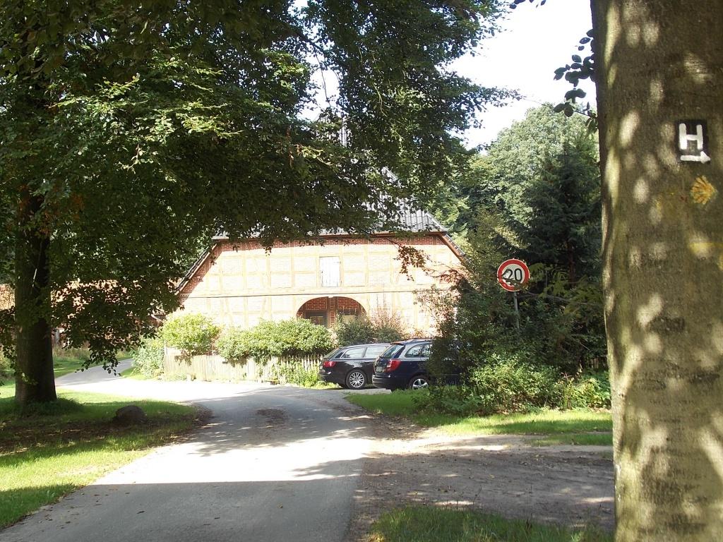 Einspurige Straße, ein altes Bauernhaus und rechts am Baum ist das weiße H auf schwarzen Grund, das der Heidschnuckenweg hier rechts ab geht.
