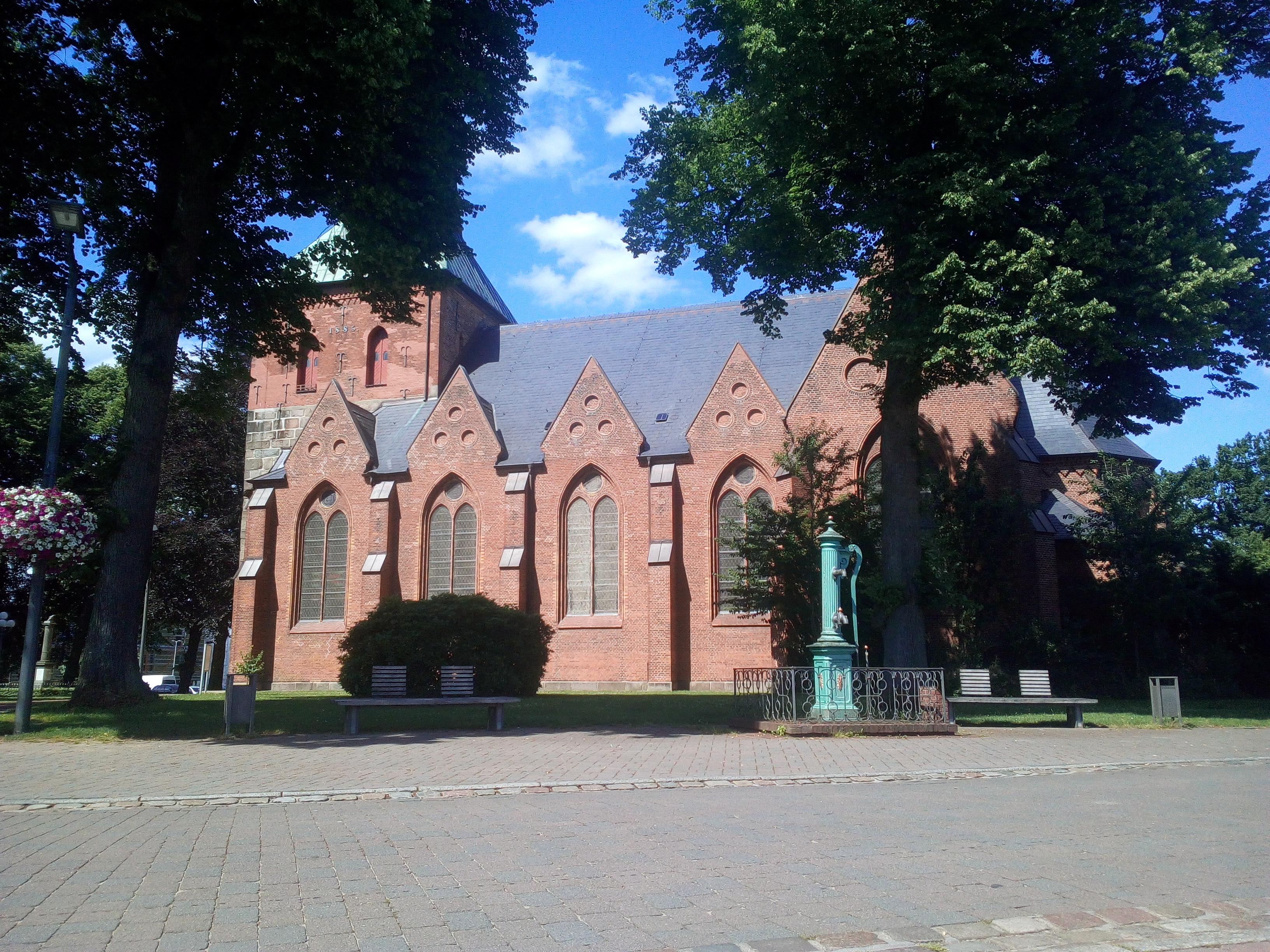Nortorf St. Martin Kirche, Bäume und die Kirche im Hintergrund.